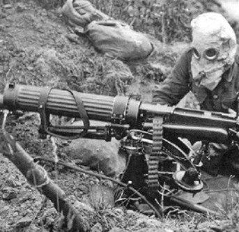 Soldier with machine gun and also wearing a gas mask.